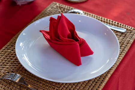 Elegant table setting with fork, spoon, white plate and red napkin in restaurant, close up. Nice dining table set with arranged silverware and napkins