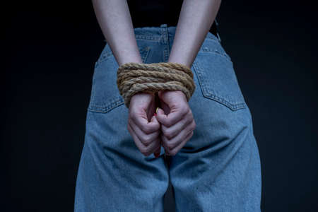 Young girl with bound hands on black background. Woman violence concept. Close up