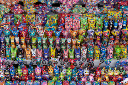 Sale of souvenirs - funny handmade wooden animals in street market. Bright colorful children toys and decoration for interior. Ubud, Bali island, Indonesia. Close up