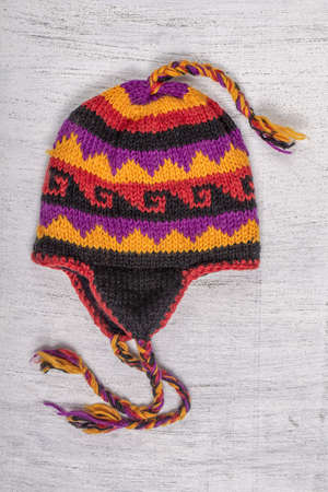 Colorful handmade knitted hats on wooden background for sale on Nepalese market, close up Imagens