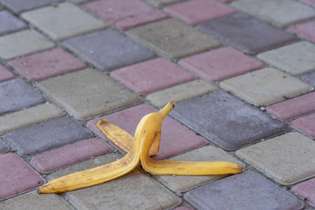 Banana peel was left on the pavement. The danger may slip. If anyone walks on it. Be careful of slippery. Close up, outdoors