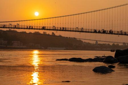 Beautiful view of Ganges river water and Ram Jhula bridge at sunset. Rishikesh, India