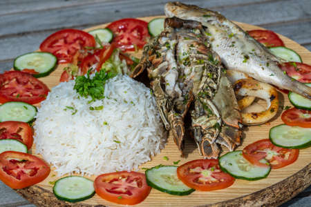 White rice with seafood and vegetables, close up. Fish, squid, shrimp, rice, tomato and cucumber in the restaurant on the island of Zanzibar, Tanzania, east Africa 写真素材