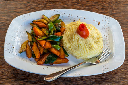 Mashed potatoes with fried vegetables on a white plate, close up