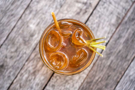 Healthy, refreshing drink of cinnamon and stalks of lemongrass on a wooden table, top view, close up