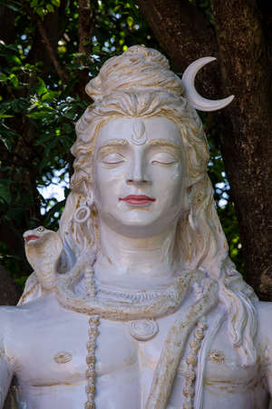 Sculpture of the Indian god Shiva, Hindu idol near Ganges river, Rishikesh, India. Statue stand near Gang river, close up