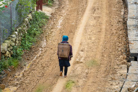 A barefoot ethnic Hmong woman walks along a dirt road after rain on the street in mountain village Sapa, North Vietnam