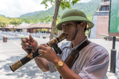 Danang, Vietnam - june 27, 2020: Vietnamese old man smoking a pipe on the street in city Da Nang, Vietnam Editorial