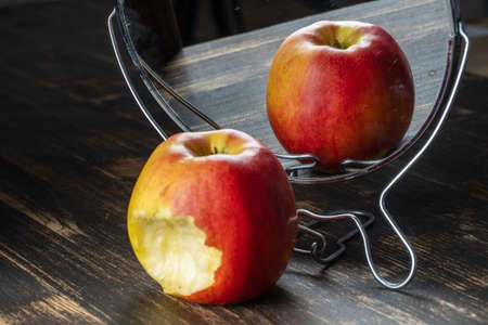 The bitten apple is reflected in the mirror, close up. Cheating concept 免版税图像