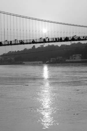 Beautiful view of Ganges river water embankment and bridge at sunset. Rishikesh, India. Black and white