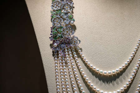 Pearl luxury necklace with precious stones in white golden frame on neck stand display in mannequin, close up