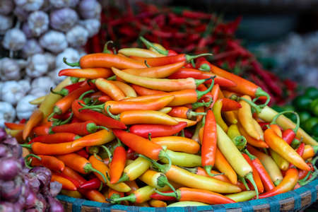 Orange, yellow and red sweet peppers for sale at street food market in the old town of Hanoi, Vietnam. Close up