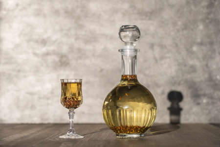Homemade birch buds tincture in a glass bottle and a wine crystal glass on a wooden table background, Ukraine, close up. Herbal alcoholic drinks concept
