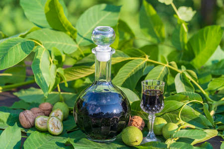 Liqueur from young green walnuts, remedy for stomach ache, close up. Tincture of green walnuts in a glass bottle on a table in the garden