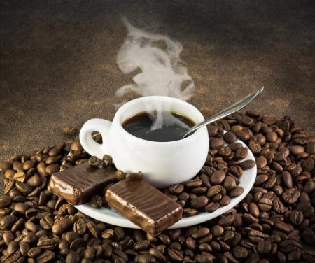 cup of coffee with the candy on the background of grains photo