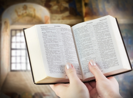 Priest:  bible in the hands of the background of old icons Stock Photo