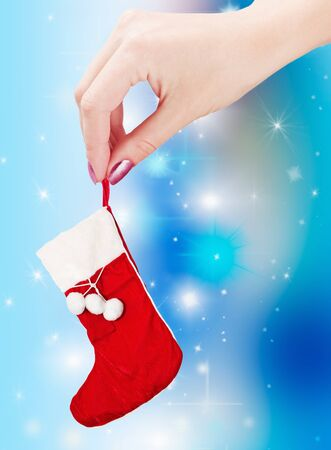 the hand holding a christmas sock on a blue background  photo