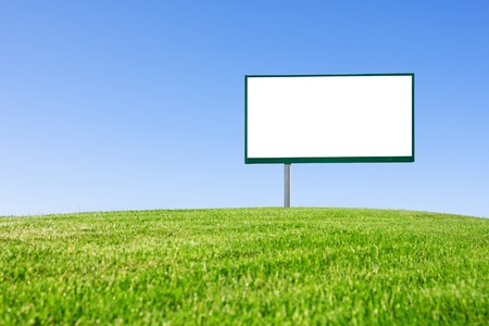 Blank billboard on green field and the blue sky in background photo