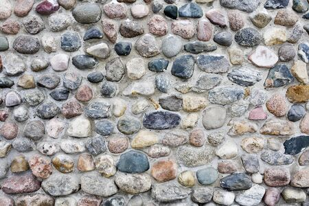 A stacked stone wall texture. The texture repeats seamlessly both vertically and horizontally. Stock Photo