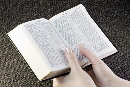 hand holds the bible on the background fabric photo