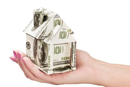 mano con dinero: mano sostiene una casa hecha de d�lares Foto de archivo