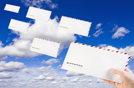 mailing envelope in his hand against the background of clouds