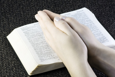 Prayer on the open Bible (focus on hands) photo