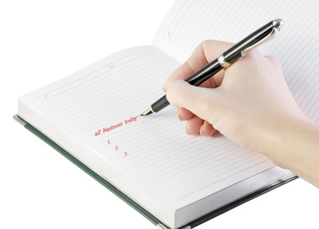 hand with pen writes in notebook isolated on white photo