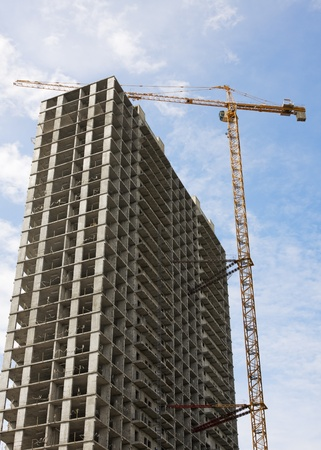 crane parts: construcci�n de un rascacielos sobre un fondo de cielo azul Foto de archivo