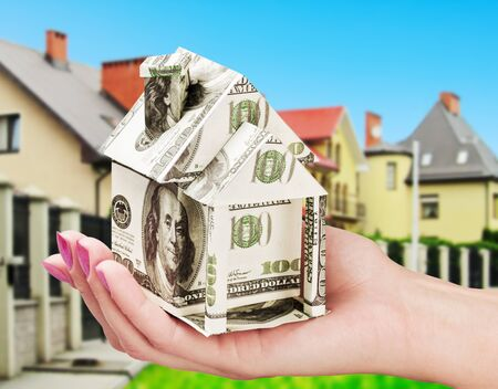 house of the money in his hand on the background of a new home Stock Photo - 11931923