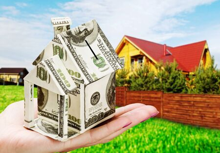 house of the money in his hand on the background of a new home photo