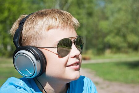 boy listening to music through headphones on the nature photo