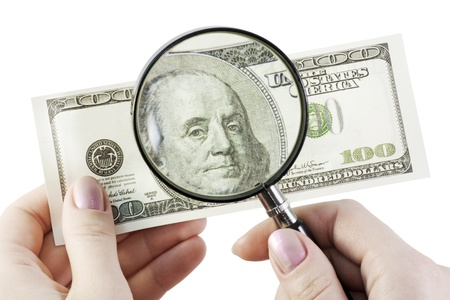 Isolated hands using a magnifying glass to see US dollar bill  Stock Photo - 12832305