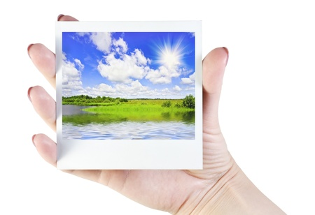 polaroid photos of landscape in hand isolated on white photo