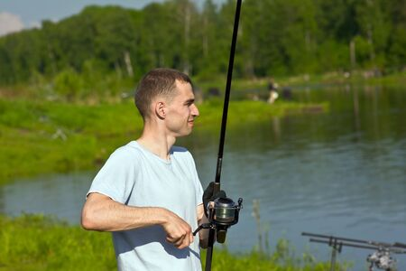 fishingline: man with a fishing rod while fishing on the lake Stock Photo
