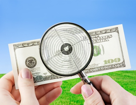 hands using a magnifying glass to see US dollar bill  Stock Photo - 12833887