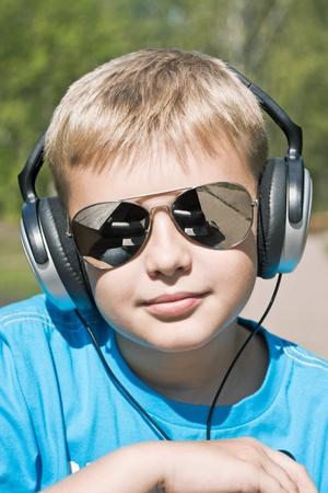 boy listening to music through headphones on the nature photo