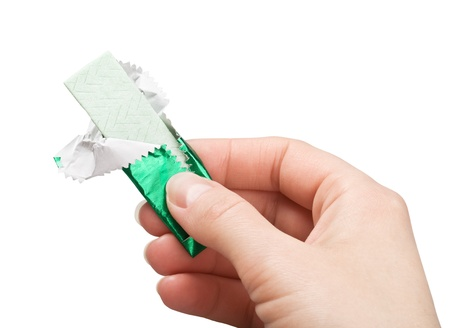 goma de mascar: la goma de mascar en la mano aisladas sobre fondo blanco
