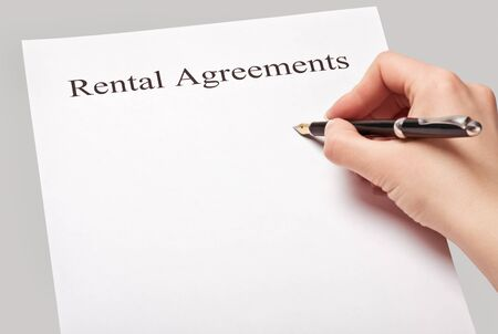 sign a rental contract on a gray background photo