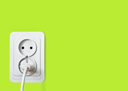 White electric socket on the green wall   photo