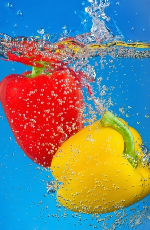 red and yellow pepper are dropped into water photo