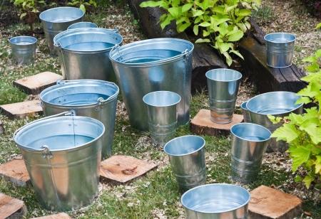 steel bucket: zinc bucket of water standing on the grass