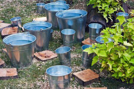 seau d eau: seau en zinc de l'eau stagnante sur l'herbe Banque d'images