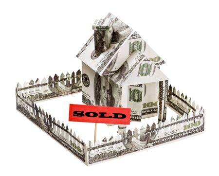 investment real state: se vende una casa hecha de dinero aisladas sobre fondo blanco