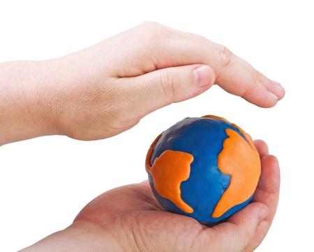 plasticine globe symbolizing the land in the hands of men isolated on white photo