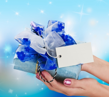 Blue gift in a female hand on the background of stars photo