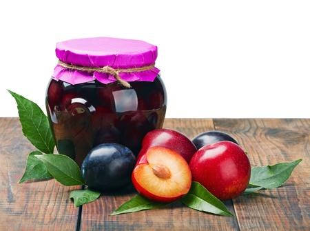 frutta sciroppata: composta di frutta in scatola e prugne fresche isolato su sfondo bianco