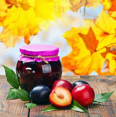 frutta sciroppata: composta di frutta in scatola e prugne fresche su uno sfondo di foglie di autunno