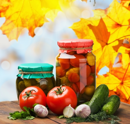 fresh and canned vegetables with herbs on a background of autumn leaves photo