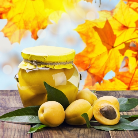 fresh and canned apricot on a background of autumn leaves photo